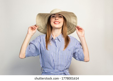 Portrait of a young friendly woman with a smile in a dress and a wide-brimmed hat on an isolated light background. Emotional face. Gesture of surprise, joy