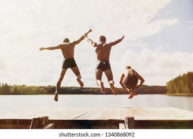 Portrait of young friends jumping from jetty into lake at sunny day. Having summer fun, enjoying life, active lifestyle and vacations concept.