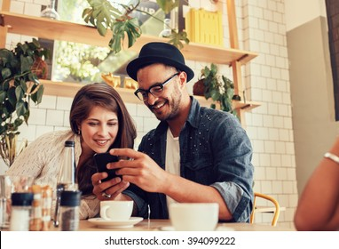 Portrait of young friends sitting in cafe looking at the photos on mobile phone. Happy young people meeting in a restaurant using cell phone.
