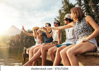 Portrait of young friends sitting on a pier and toasting beers. Happy young men and women having beers at the lake on a sunny day.