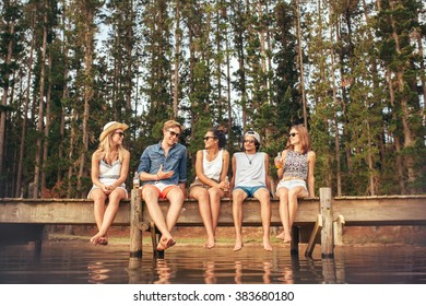 Portrait of young friends sitting on jetty and talking. Young men and women enjoying a day at the lake.