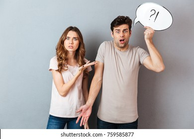 Portrait of a young frustrated couple having an argument while standing and holding speech bubble isolated over gray wall