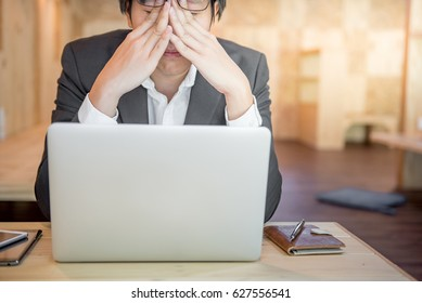 Portrait of young frustrated stressed business man with modern laptop computer and leather notebook on wooden office desk in workplace, overworked and depression concepts, Feeling sick and tired