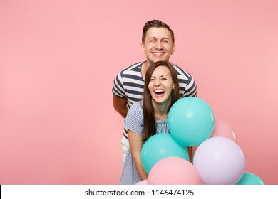 Portrait of young fun crazy mad couple in love. Woman and man in blue clothes celebrating birthday holiday party on pastel pink background with colorful air balloons. People sincere emotions concept