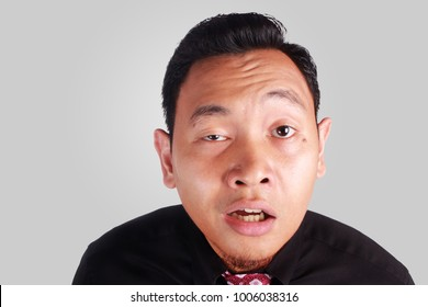 Portrait of young funny Asian man mocking and showing stupid silly ridiculous facial expression