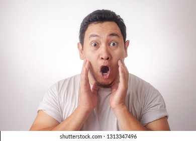 Portrait of young funny Asian man in white shirt, gesturing shocked or surprised expression with mouth open, while standing over grey background