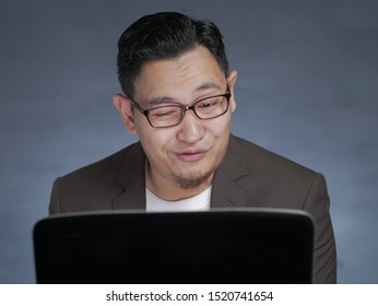 Portrait of young funny Asian man smiling naughty when looking at his laptop, watching porn online