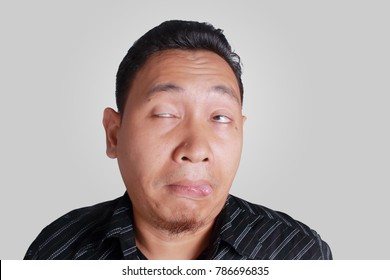 Portrait of young funny Asian man mocking and showing stupid silly ridiculous drunk facial expression