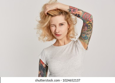 Portrait of young gil wearing ring in nose and tattoes over her arms touching and correct her hairstyle. Wink. Isolated over white wall