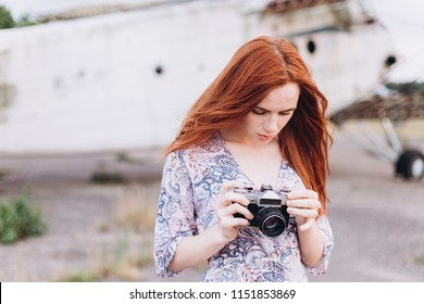 Portrait of a young ginger caucasian girl with freckles taking photos outdoors. Gorgeous woman phtographer posind with camera in summer
