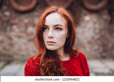 Portrait of a young ginger redheaded sexy gorgeous natural girl with long hair and freckles on face posing in autumn outdoors in park