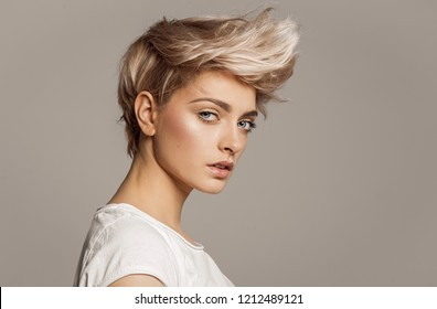Portrait of young girl with blond fashion hairstyle looking at camera isolated on gray background