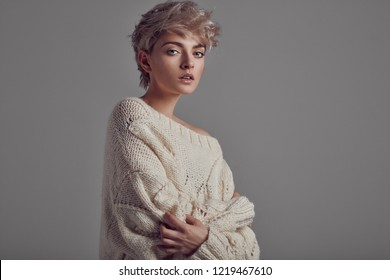 Portrait of young girl with blond hair wear sweater looking at camera isolated on gray background