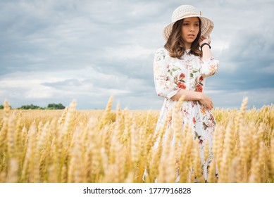 portrait of a young girl with blond long hair with a happy smile on her face, looks straight, straightens her hat, wears a light dress and a light hat, standing in field or meadow in summer or autumn