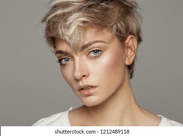 Portrait of young girl with blond short hairstyle looking at camera isolated on gray background with copy space