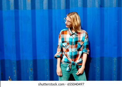 Portrait of a young girl of the blonde in glasses on a background the blue iron wall