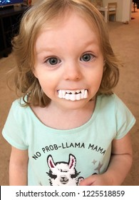 Portrait of young girl with blonde hair wearing a no prob-llama mama t-shirt and white vampire teeth