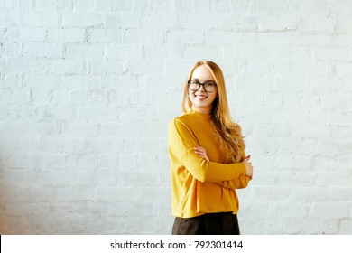 Portrait of the young girl of the blonde with a yellow sweater against the background of a white brick wall. Woman  smiles and holds a hand on a waist. Copy space. Wears glasses