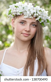 Portrait of a young girl in blossoming apple trees