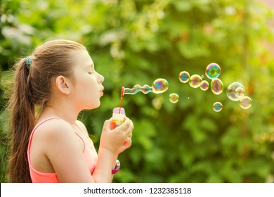 Portrait of a young girl blowing soap bubbles in a park
