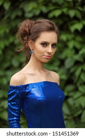 Portrait of a young girl in a blue dress on the background of green foliage