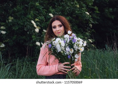 Portrait of a young girl with a bouquet of wildflowers on a forest background. The photo was tinted and has a slight noise to create a film photo effect.