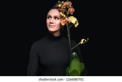 Portrait of young girl with bright orchid on black background