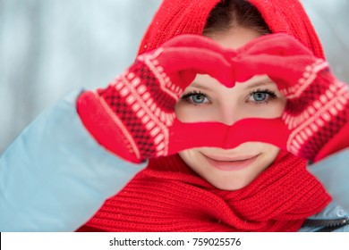 Portrait of a young girl close-up, wearing red gloves and a scarf, holding hands in the shape of a heart. Heart symbol shaped Lifestyle and Feelings concept.