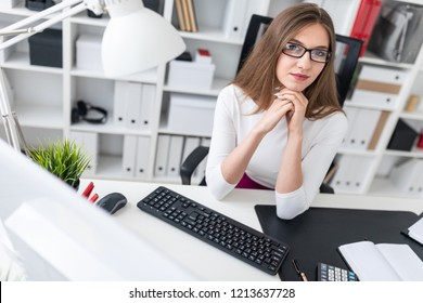 Portrait of a young girl at a computer Desk in the office.