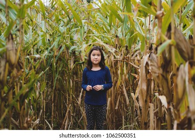 Portrait of a young girl in a corn maze.