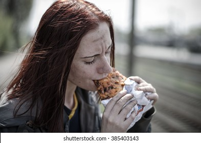 portrait of a young girl with a dirty face, in old dirty clothes, eating a slice of pizza. Homeless girl.