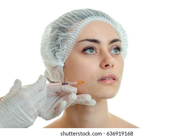 Portrait of a young girl at the doctor who makes an analgesic injection on the face in white gloves close-up