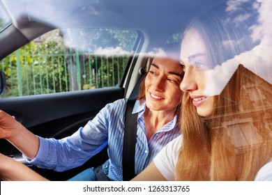 Portrait of young girl driving car with her mother
