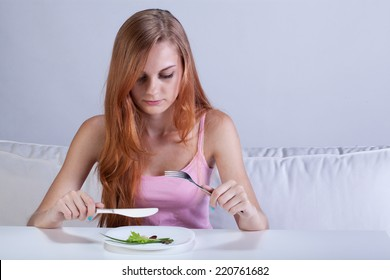 Portrait of young girl eating very small lunch