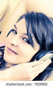 Portrait of Young Girl enjoying listening music in headphones - cross-processed