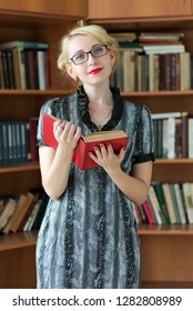Portrait of a young girl in glasses with a book in the library