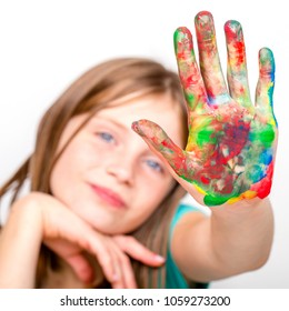 Portrait young girl and hands painted in colorful paints, close up