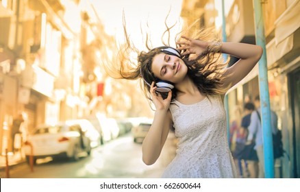 Portrait of a young girl having fun and listening music with headphones.