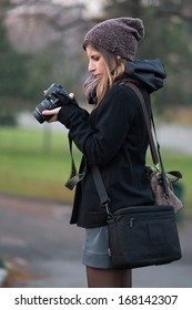 Portrait of young girl with her reflex DSLR in one city park while checks the last picture - Bologna Giardini Margherita