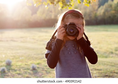 Portrait of a young girl, holding a photo camera