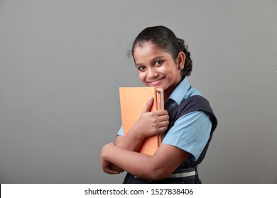 Portrait of young girl of Indian origin holding note books in her hands