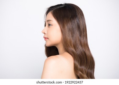 Portrait of young girl with long hair standing isolated on white background