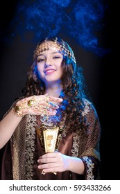portrait of a young girl with long hair in oriental dancer costume holding a censer with burning incense and the smoke poses on a black background in the scenic blue light
