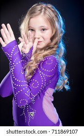 Portrait of a young girl with long hair in a violet costume oriental dancer posing and dancing on a black background in the scenic blue light