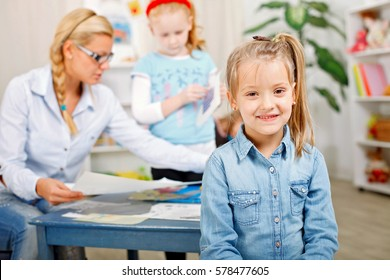 Portrait of young girl looking at camera in classroom.