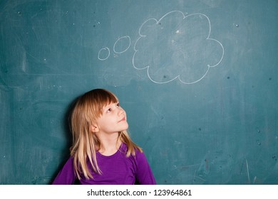 Portrait of young girl looking at empty idea bubble drawn on chalkboard