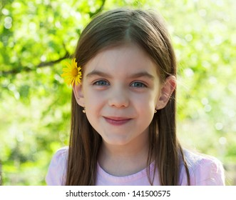 Portrait of a young girl looking into the camera with a smile on her face