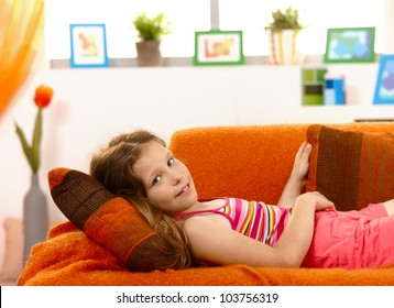 Portrait of young girl lying on couch at home, looking at camera, smiling.