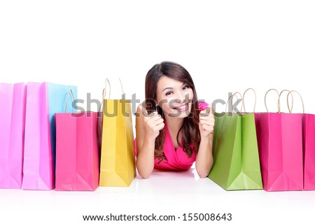 Portrait of a young girl lying with shopping bags and show thumb up isolated on white , asian beauty