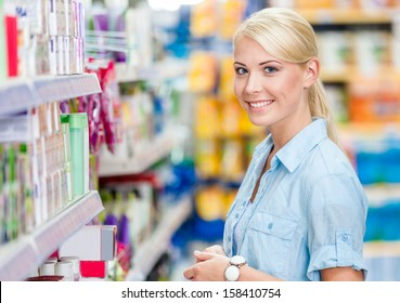 Portrait of young girl at the market standing near the shelves with cosmetics